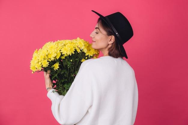 분홍색 빨간색 벽에 모자와 캐주얼 흰색 스웨터에 세련 된 여자