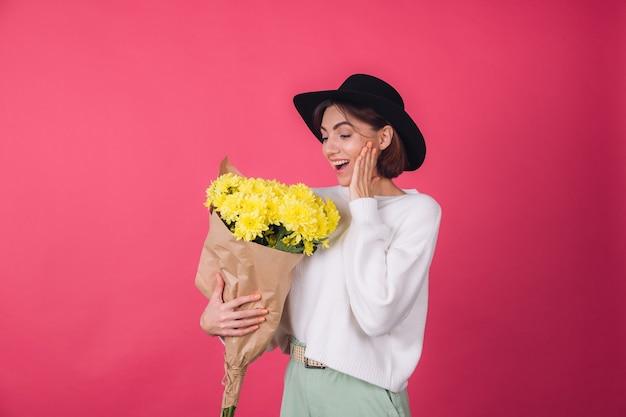 Стильная женщина в шляпе и повседневном белом свитере на красной стене