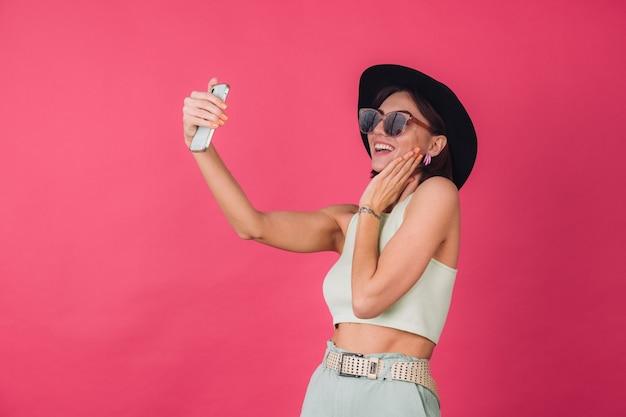 분홍색 빨간 벽에 모자와 선글라스에 세련 된 여자