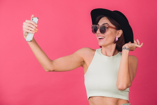 ピンクの赤い壁に帽子とサングラスのスタイリッシュな女性