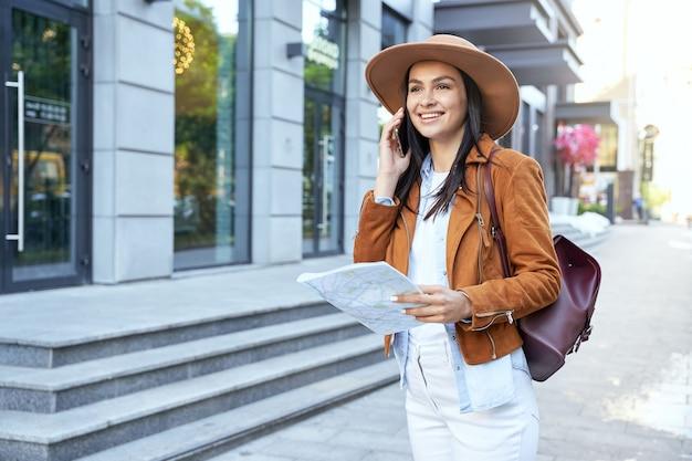街の地図を保持している帽子のスタイリッシュな女性