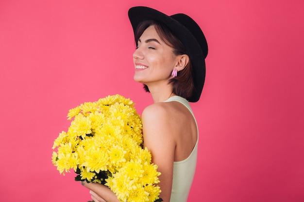 Стильная женщина в шляпе, обнимая большой букет желтых астр, весеннее настроение, спокойное улыбающееся изолированное пространство