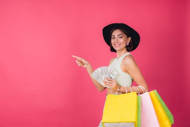 Стильная женщина в шляпе на розовой красной стене
