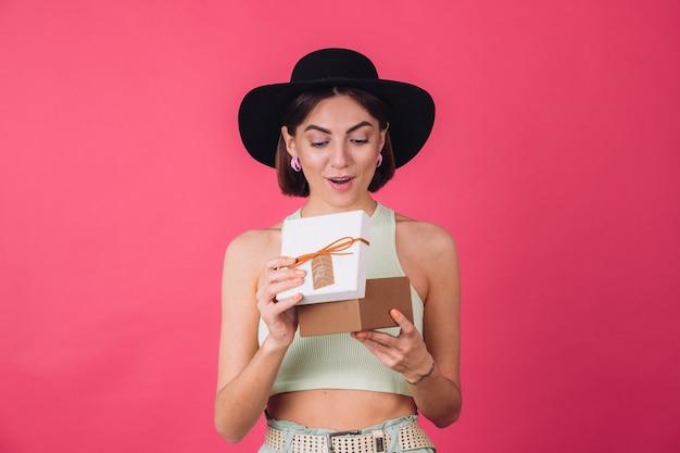 ピンクの赤い壁に帽子をかぶったスタイリッシュな女性