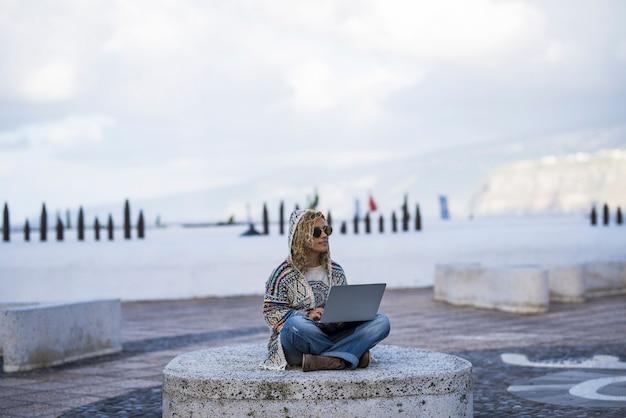 パーカーとサングラスを身に着けたスタイリッシュな女性が、ノートパソコンを使用して足を組んで屋外に座って、何か面白いものを賞賛しています。屋外でテクノロジーとインターネットを扱う女性