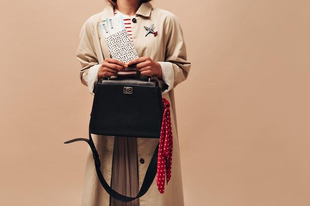 Стильная женщина в длинном осеннем пальто и современном полосатом свитере держит черную сумочку и билеты на изолированном бежевом фоне.