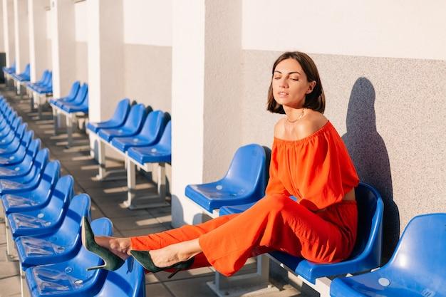サイクルトラックスタジアムのポーズで日没時にオレンジ色の服を着たスタイリッシュな女性