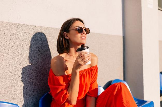 コーヒーのカップとサイクルトラックスタジアムで日没時にオレンジ色の服を着たスタイリッシュな女性