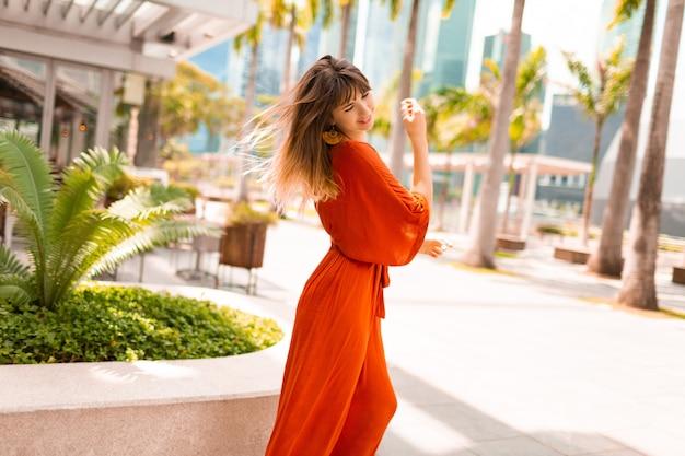 Стильная женщина в оранжевом платье позирует на набережной с пальмами и небоскребами в большом современном городе