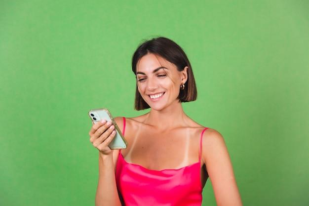 휴대 전화 화면에 미소 표정으로 행복 녹색에 고립 된 핑크 실크 드레스에 세련된 여자, 메시지 뉴스 읽기