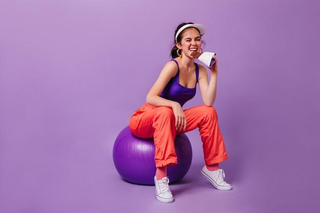 보라색 상단과 빨간색 스웨트 팬츠에 세련된 여자가 보라색 벽에 fitball에 앉아 초콜릿 바를 먹는다
