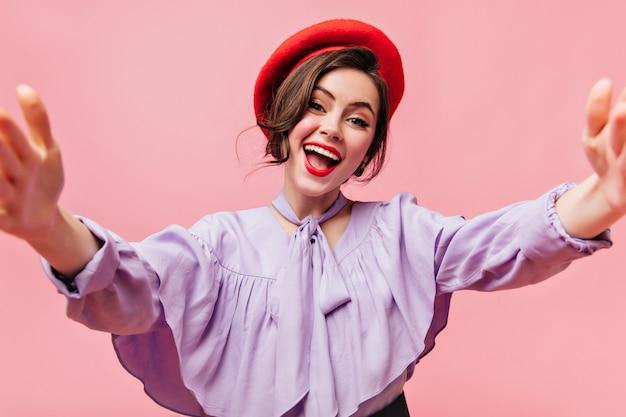 赤いベレー帽と紫のブラウスのスタイリッシュな女性は笑顔でピンクの背景に自分撮りをします。