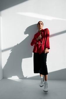 赤いブレザーとズボンのスタイリッシュな女性のファッショナブルな秋の靴は、古典的な肖像画に合います。高品質の写真