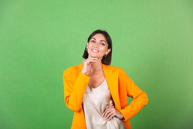 グリーンにシルク ベージュのドレスとオレンジ色の特大ブレザーを着たスタイリッシュな女性、ポジティブな感情が微笑む