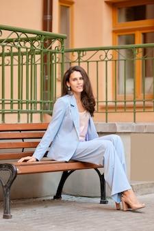 Skyblue pantsuit의 세련된 여자가 사무실 근처 벤치에서 휴식을 갖는