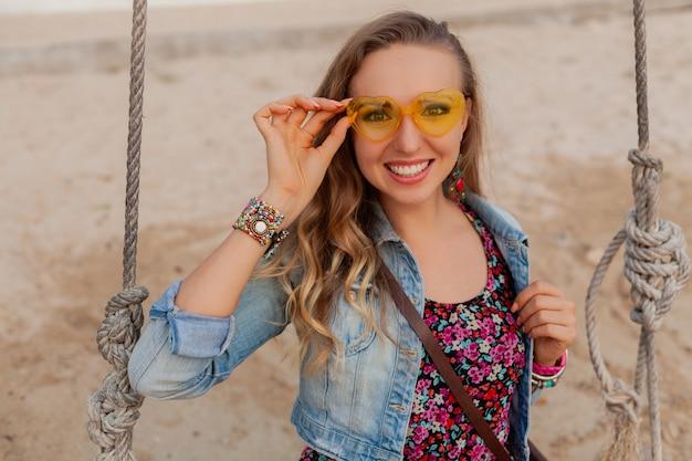 幸せな笑顔のカラフルな黄色の太陽ガラスのビーチで夏のドレス休暇のスタイリッシュな女性