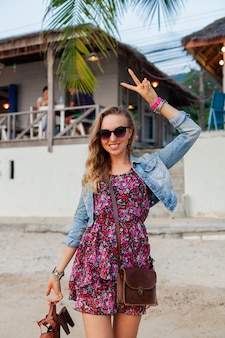 手に靴を持ってビーチを歩く夏のドレス休暇のスタイリッシュな女性