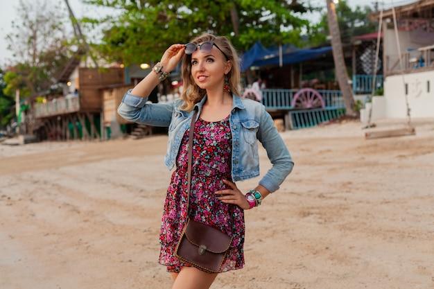 サングラスとビーチを歩く夏のドレス休暇でスタイリッシュな女性