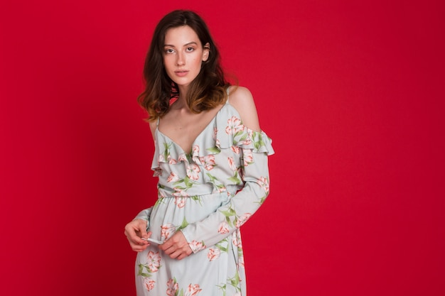 Стильная женщина в летнем модном платье позирует на красном