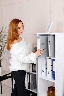 ビジネスペーパーフォルダーを持つオフィスでスタイリッシュな女性