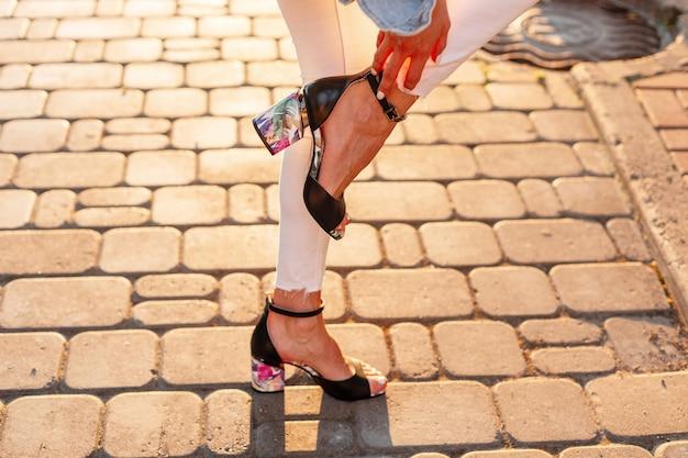 우아한 가죽 샌들을 신고 세련된 흰색 청바지를 입은 세련된 여성은 화창한 날 야외 돌길에 한쪽 다리로 서 있습니다.