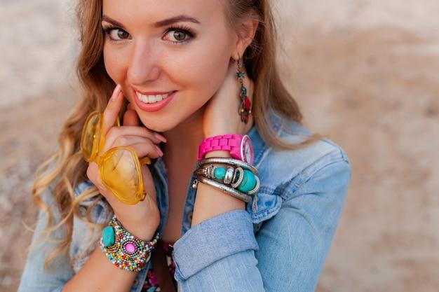 幸せなアクセサリージュエリーを笑顔のカラフルな黄色のサングラスでビーチで休暇中のスタイリッシュな女性