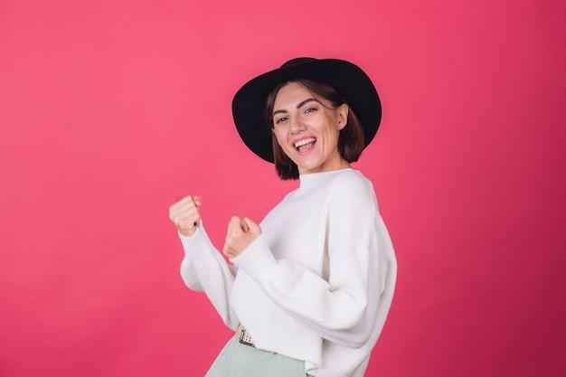 赤ピンクの壁に白いカジュアルセーターと帽子のスタイリッシュな女性