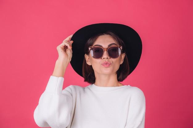 赤ピンクの壁に白いカジュアルセーター、サングラス、帽子のスタイリッシュな女性