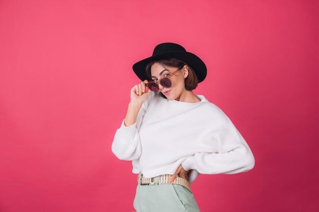 빨간색 분홍색 벽에 흰색 캐주얼 스웨터, 선글라스와 모자에 세련된 여자