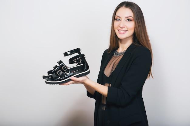 靴のペイトを保持している黒のスーツで分離されたスタイリッシュな女性