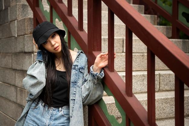 Stylish woman in k-pop clothing in urban scene