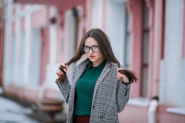 冬に一人で街の通りを歩くコートを着たスタイリッシュな女性モデル