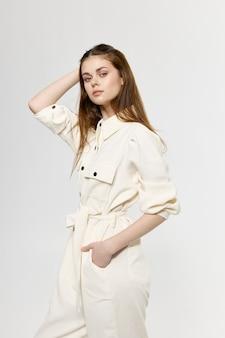 Стильная женщина-модель в белом костюме на свете держит руку за голову