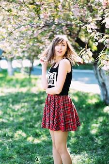 사쿠라 피 나무 근처 세련 된 여자입니다. 피 나무에 소녀입니다. 봄 개념