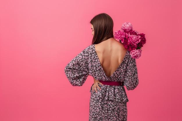Стильная женщина на розовом в летнем модном платье позирует с букетом цветов пиона, вид со спины