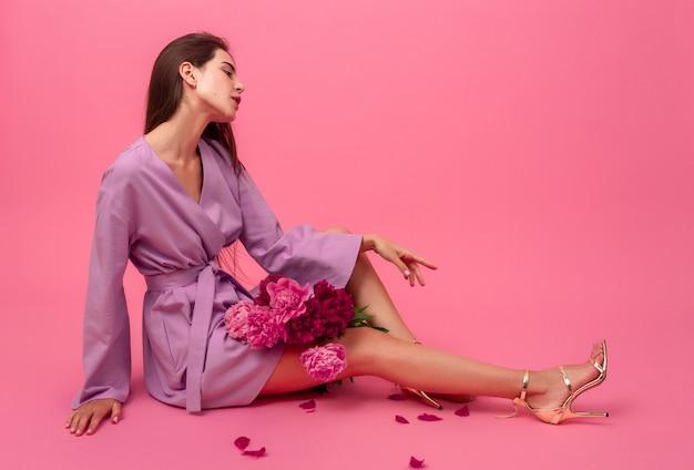 床に座って牡丹の花の花束でポーズ夏バイオレットミニトレンディなドレスでピンクのスタイリッシュな女性