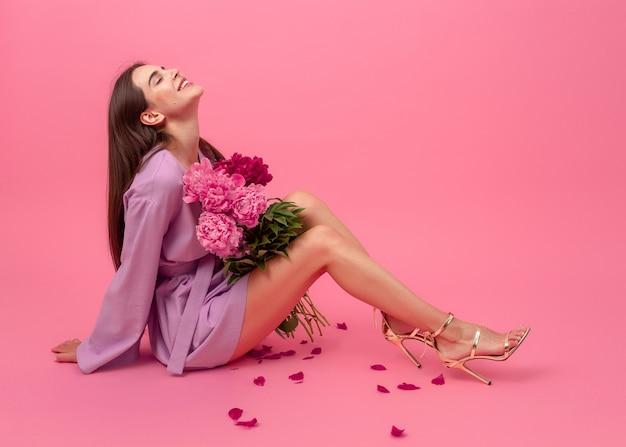 Стильная женщина на розовом в летнем фиолетовом модном мини-платье позирует с букетом цветов пиона, сидя на полу