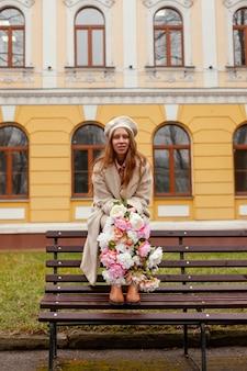 야외에서 봄에 꽃의 꽃다발을 들고 벤치에 세련된 여자