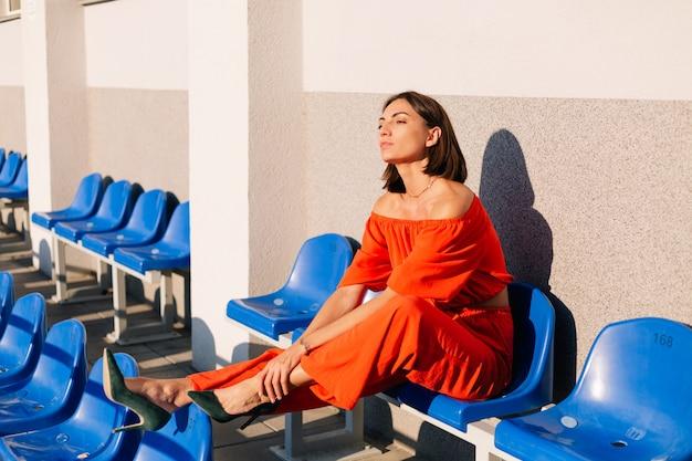 Donna alla moda in vestiti arancioni al tramonto alla posa dello stadio della pista ciclabile