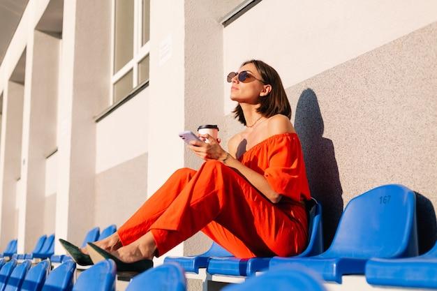 Donna alla moda in abiti arancioni al tramonto allo stadio della pista ciclabile con una tazza di caffè e un telefono cellulare