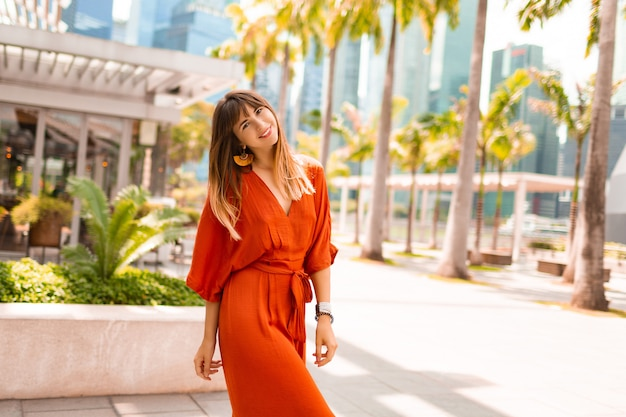 Stylish woman in orange dress posing on promenade with palm trees and skyscrapers in big modern city