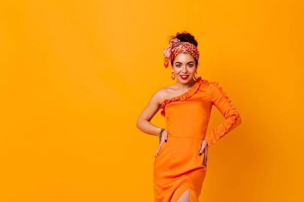 Elegante donna in abito di raso arancione e fascia luminosa sorridente e in posa su uno spazio isolato.