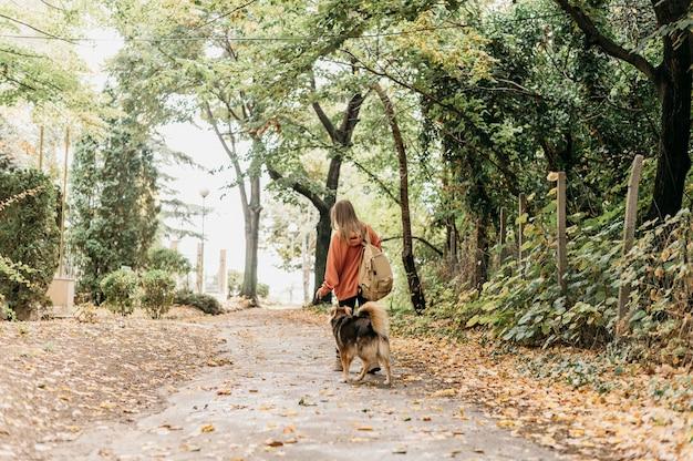 Donna alla moda a fare una passeggiata con il suo cane