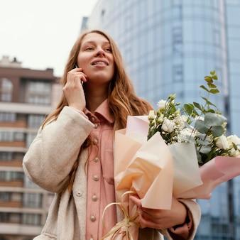 Donna alla moda all'aperto conversando al telefono e tenendo il mazzo di fiori