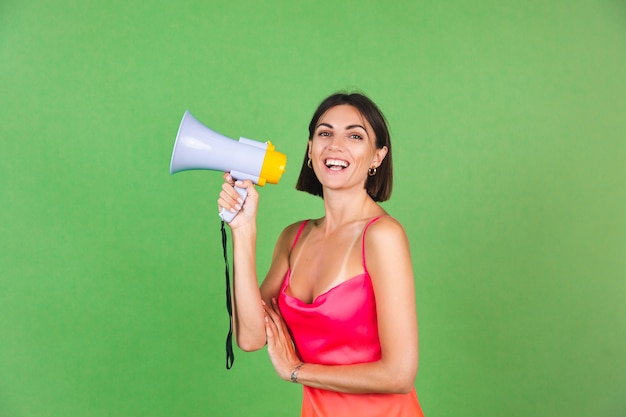 Stylish woman in pink silk dress on green, happy excited joyful cheerful shouting in megaphone, isolated