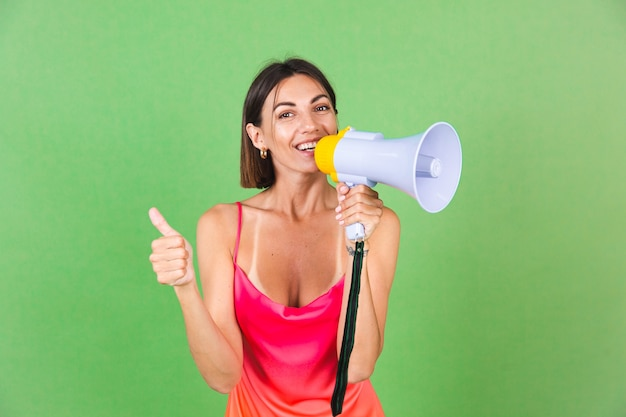 Stylish woman in pink silk dress on green, happy excited joyful cheerful shouting in megaphone, thumb up isolated