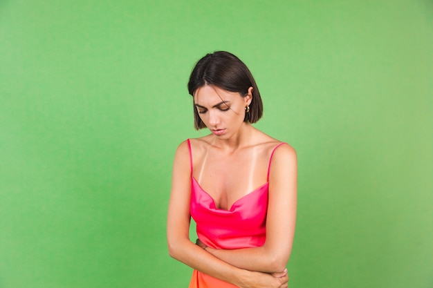 Stylish woman in pink silk dress isolated on green suffering from stomach pain