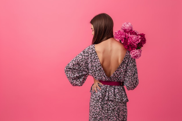 stylish woman on pink in summer trendy dress posing with peony flowers bouquet, view from back