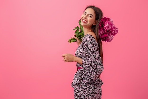 Elegante donna in rosa in abito alla moda estate in posa con bouquet di fiori di peonia