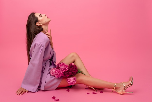 Stylish woman on pink in summer violet mini trendy dress posing with peony flowers bouquet sitting on floor